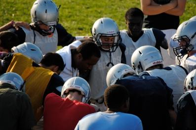 Coach Kris Ryan leads the team in prayer