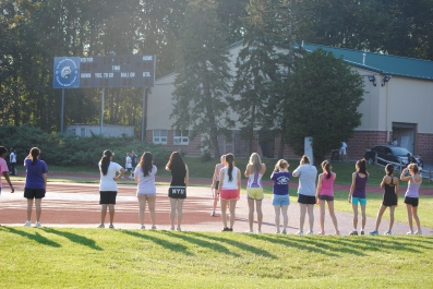 The girls cross country team does some dynamic stretching