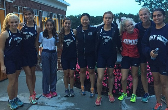 The girls' cross country team poses with the victory bell after beating Port Jeff (Photo credit: Erika Kady)
