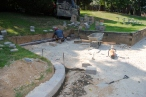A stone retaining wall goes in where the tennis storage shed will be located