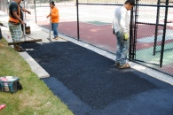 Workers lay a paved path along the courts