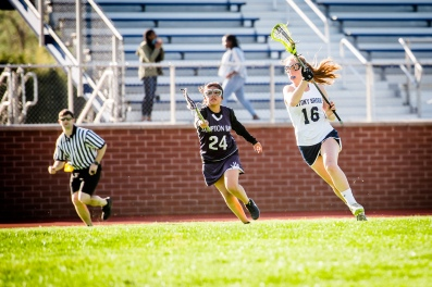 Rachel Leccese carries the ball upfield for the JV girls' lacrosse team (PC: Bruce Jeffrey)