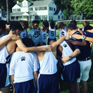 The boys pray prior to a home meet in Sept.